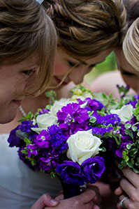 Three bridesmaids smell the scent of their bouquets