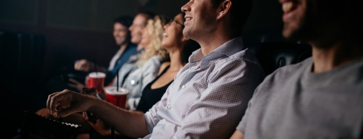 people sitting in a theater watching a film