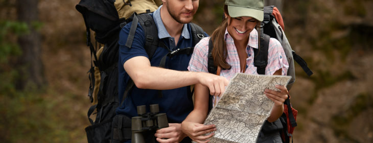 couple looking at map while hiking