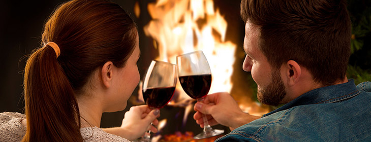 Couple in front of fireplace with red wine