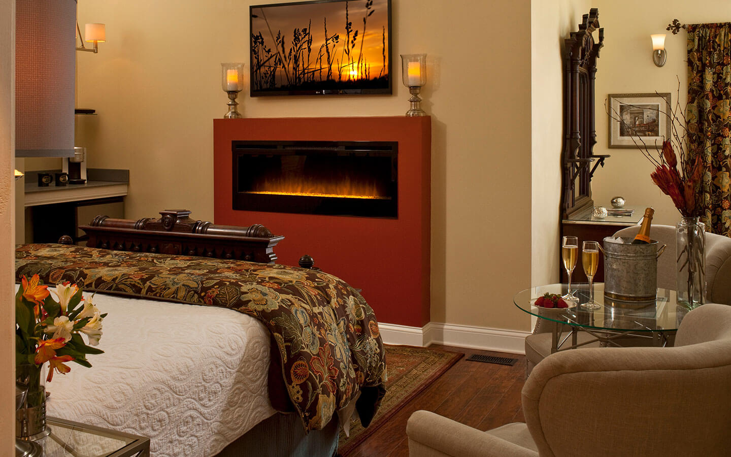 Room with a king size bed and seating area as well as a large fire plave and television