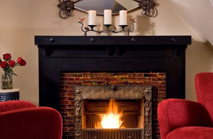 Fireplace suite, with two relaxing red chairs by the fire at our Allegan bed and breakfast