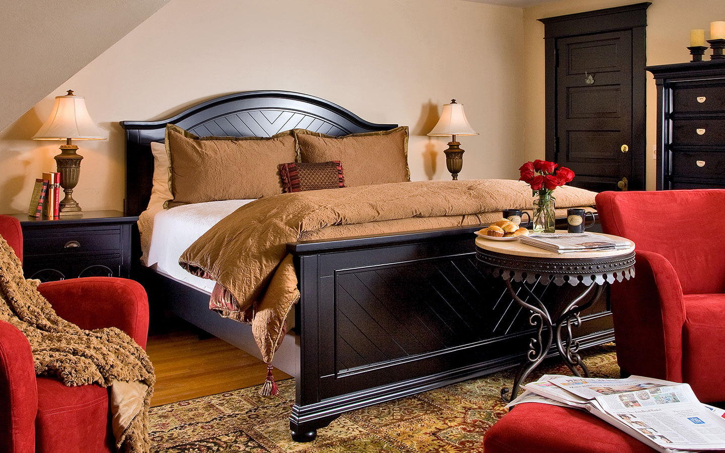 The Crowing Suite at our Allegan bed and breakfast, king bed in dark wood, table and red chairs.