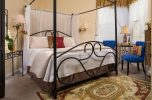 King sized wrought iron bed with two blue chairs at our Michigan romantic getaway