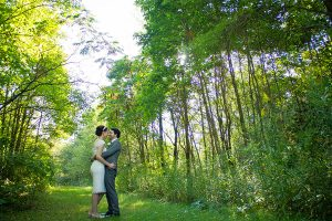 Bride and groom holding each other in a meadow with trees