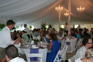 People at an outdoor wedding reception under a large white canopy