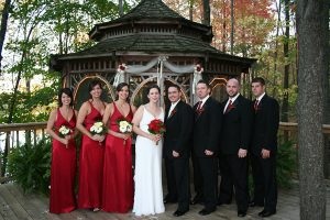 Bride, groom, bridesmaids, and groomsmen in front of decorated gazebo