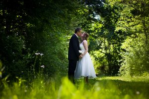 Bride and groom kissing in a grassy meadow with trees