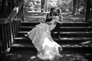 Bride and groom sitting on wooden stairs outside and kissing