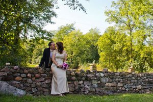 Bride sitting on a stone wall with groom standing behind