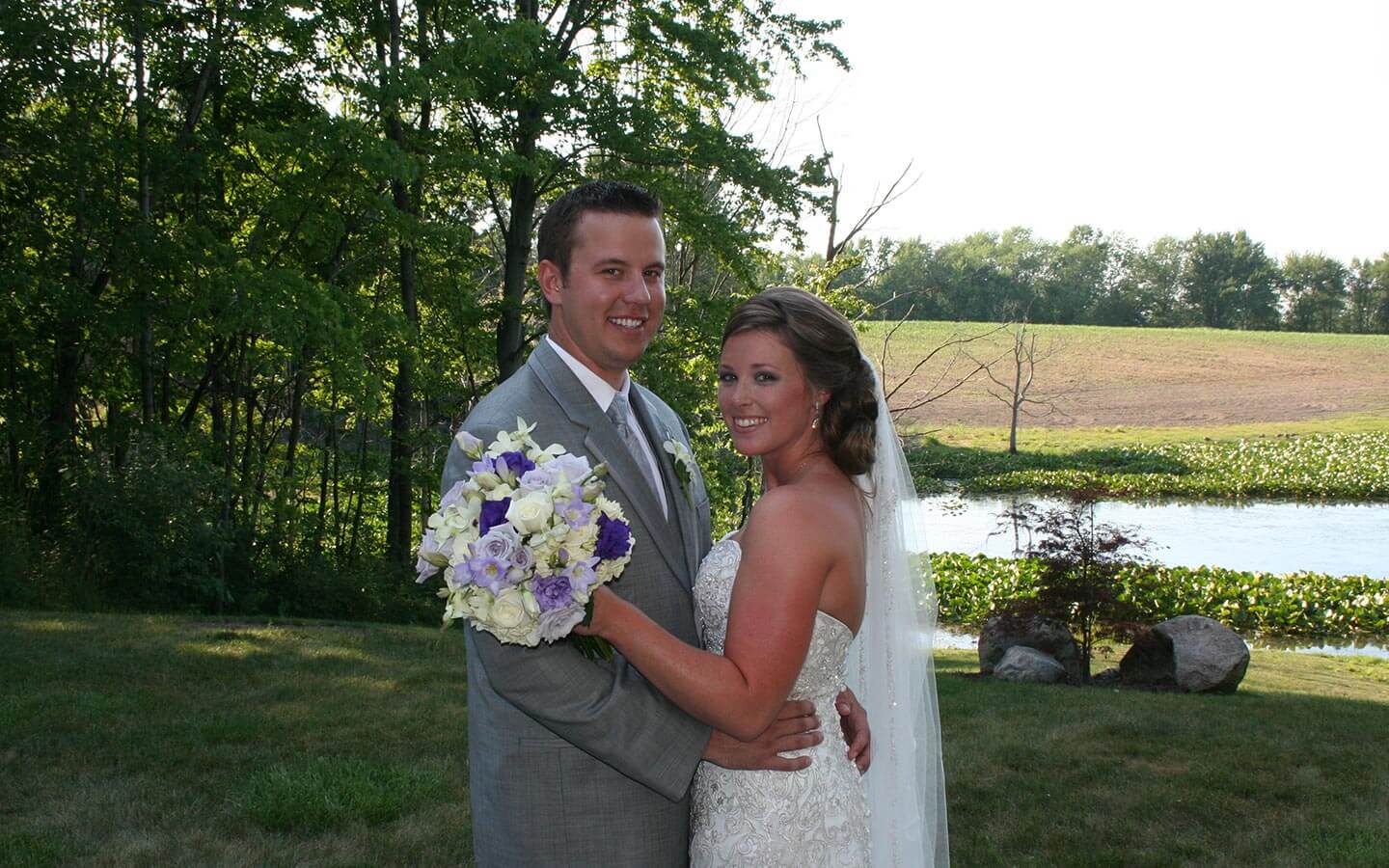 Bride and Groom smiling by the pond at a destination wedding in Michigan