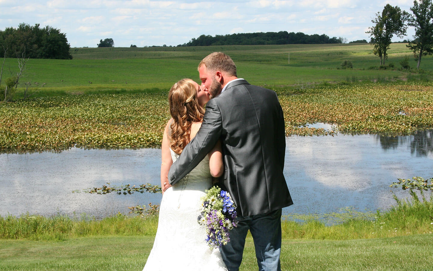 Michigan Wedding, bride and groom kissing by the pond