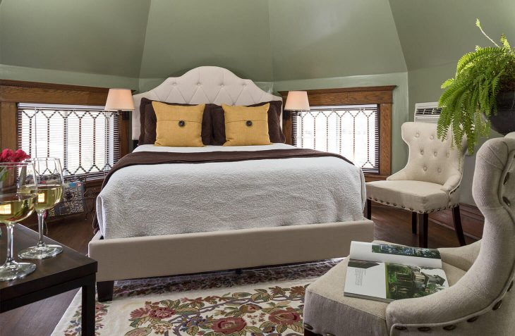 Romantic Michigan getaway, the Golden Tower room with Queen bed, sitting area & wine glasses