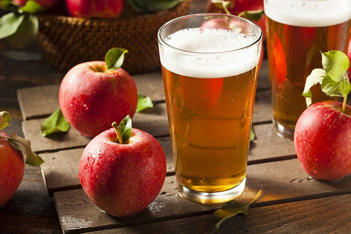 Glass of hard apple cider ale surrounded by apples
