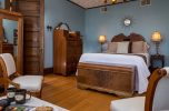 The Royalty Suite with cool blue walls, wood floor, queen bed and sitting area