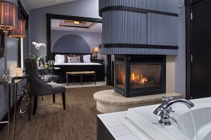 Sir Lancelot Suite bed, fireplace, side table, and tub faucet