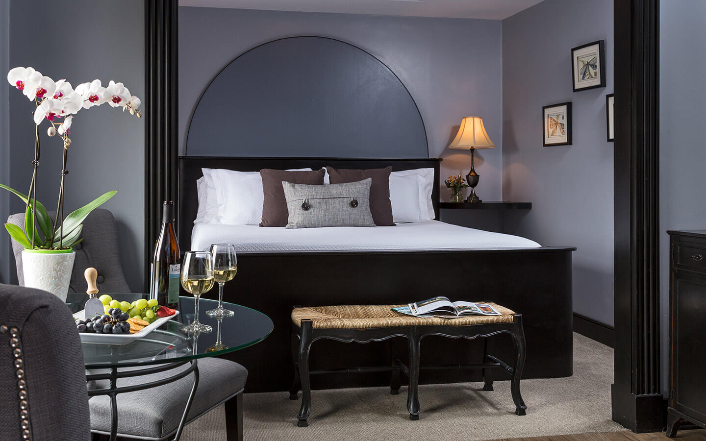 Room with a king size bed and seating area as well as a drop ceiling feature.
