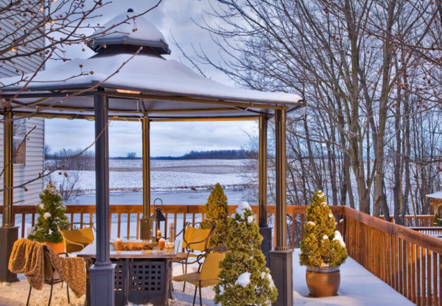 outdoor fireplace under a gazebo in the winter surrounded by snow