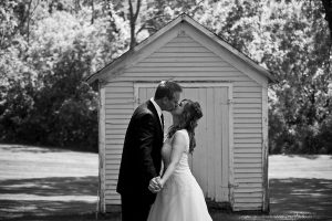 Bride and groom kissing in front of an old shed in black and white