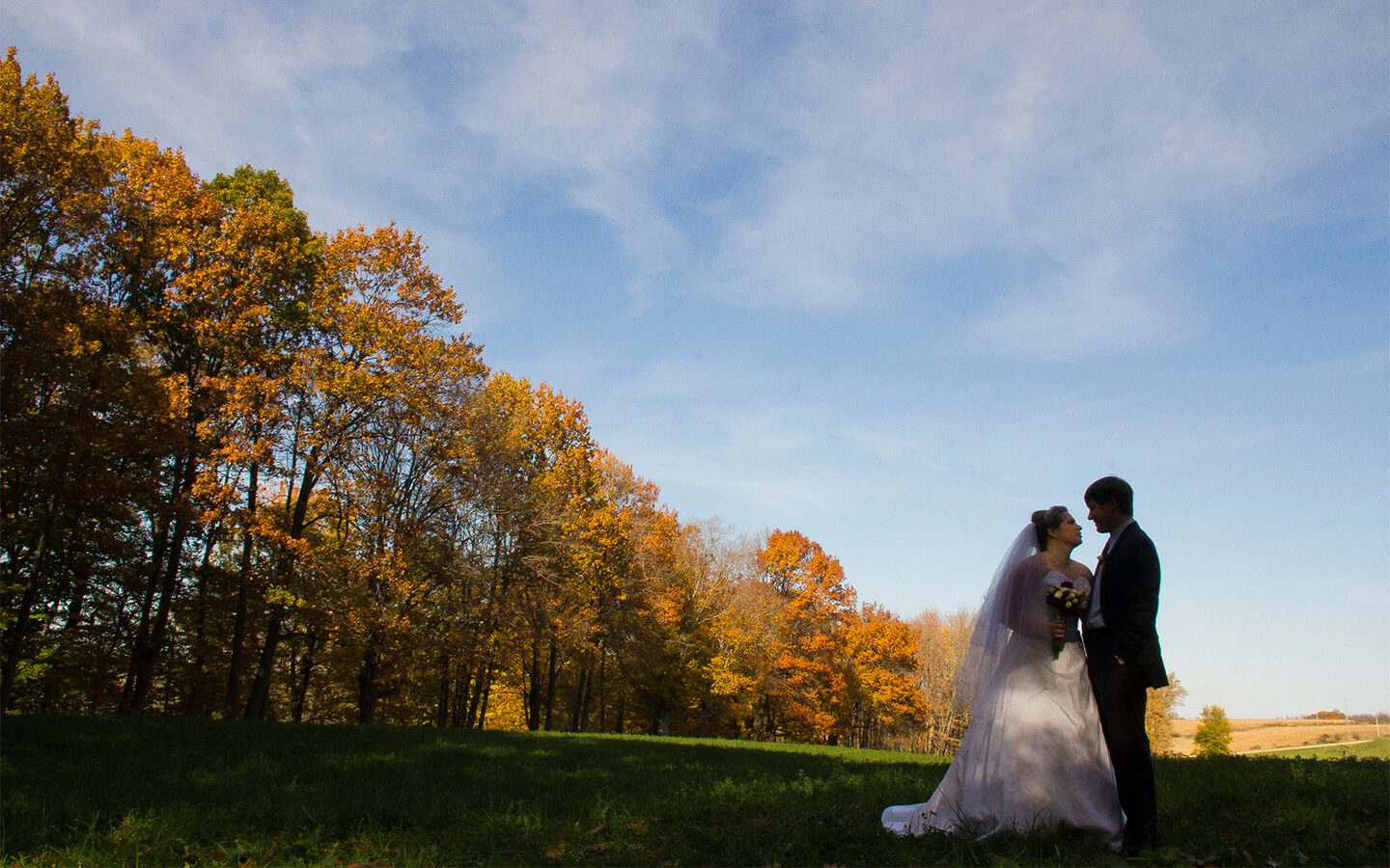Couple with fall trees in background - Elopement in Michigan