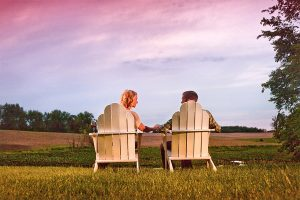 Couple sitting in white chairs outside at sunset