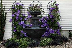 Water fountain in front of purple flowers