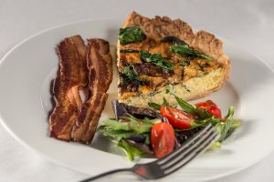 Plate of quiche with bacon and salad