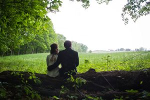 Newlywed couple sitting on a log looking at a meadow with flowers and trees