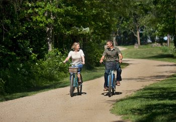 Couple riding bikes on a dirt path in Michigan