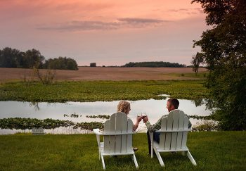 Couple drinking wine sitting in white chairs by the lake
