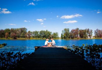Couple enjoying a picnic lunch on the dock at the lake