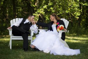 Bride and groom sitting on white chairs in the garden