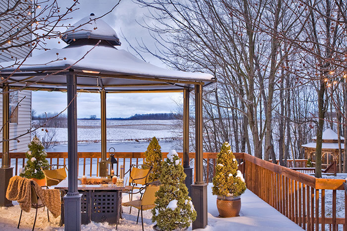 Snow on the deck with views of the frozen lake at a winter getaway in Michigan