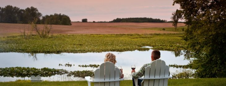 couple sitting on lawn chairs with wine overlooking the lake