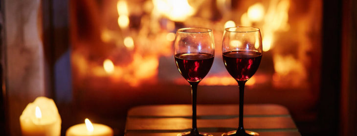 Two glasses of red wine by the fire
