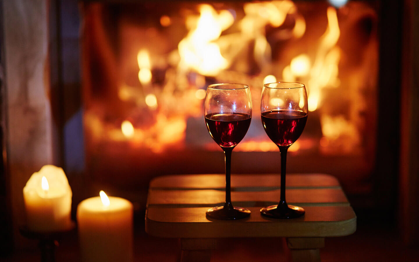2 wine glasses in front of a fireplace with candles
