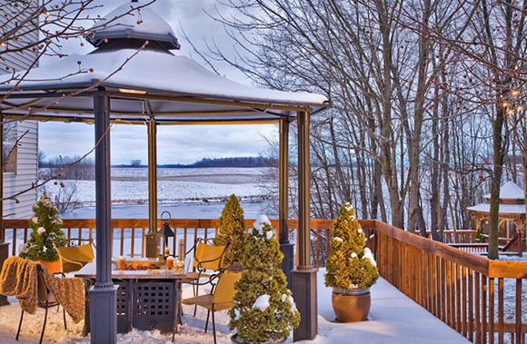 snowy covered patio with fireplace and view of the lake