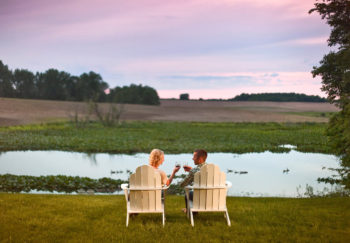 Couple drinking wine by the water at our romantic getaway in Michigan