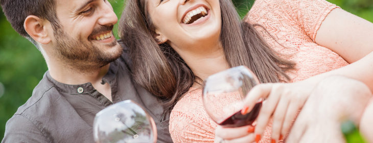 couple laughing with glasses of wine