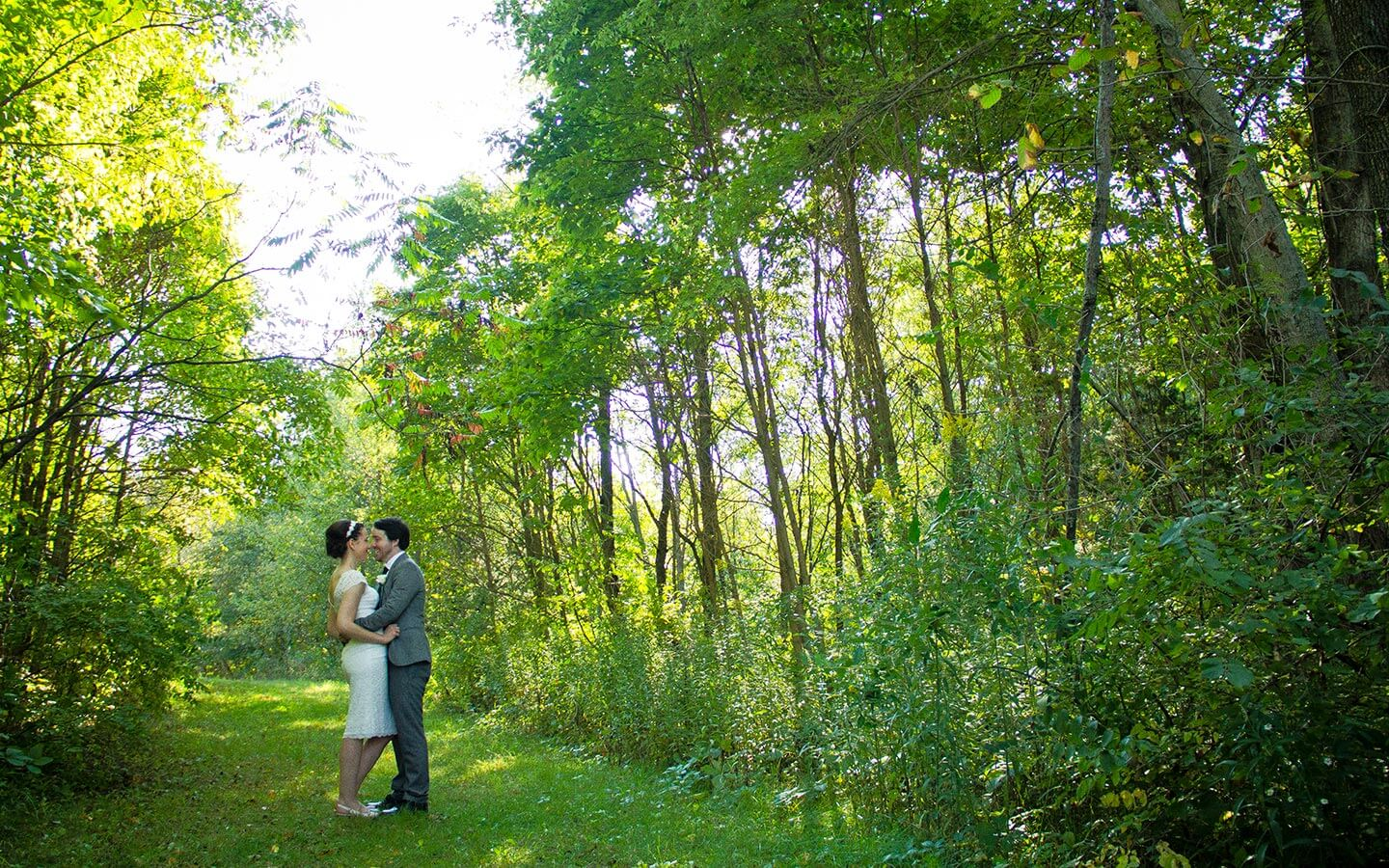 bride and groom in a field surrounded by trees