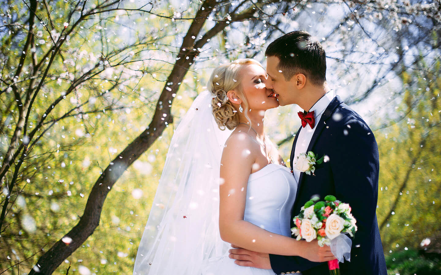 bride and groom kissing outside near trees