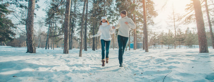Couple running on a snow trail hand-in-hand surrounded by tall pine trees