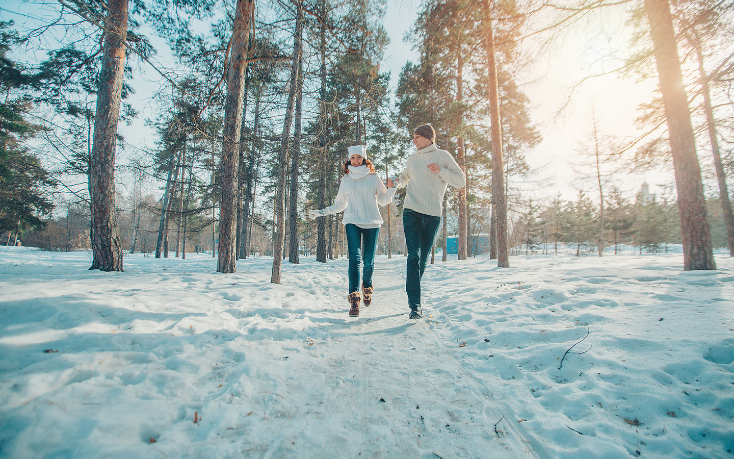 couple running in the forest in snow