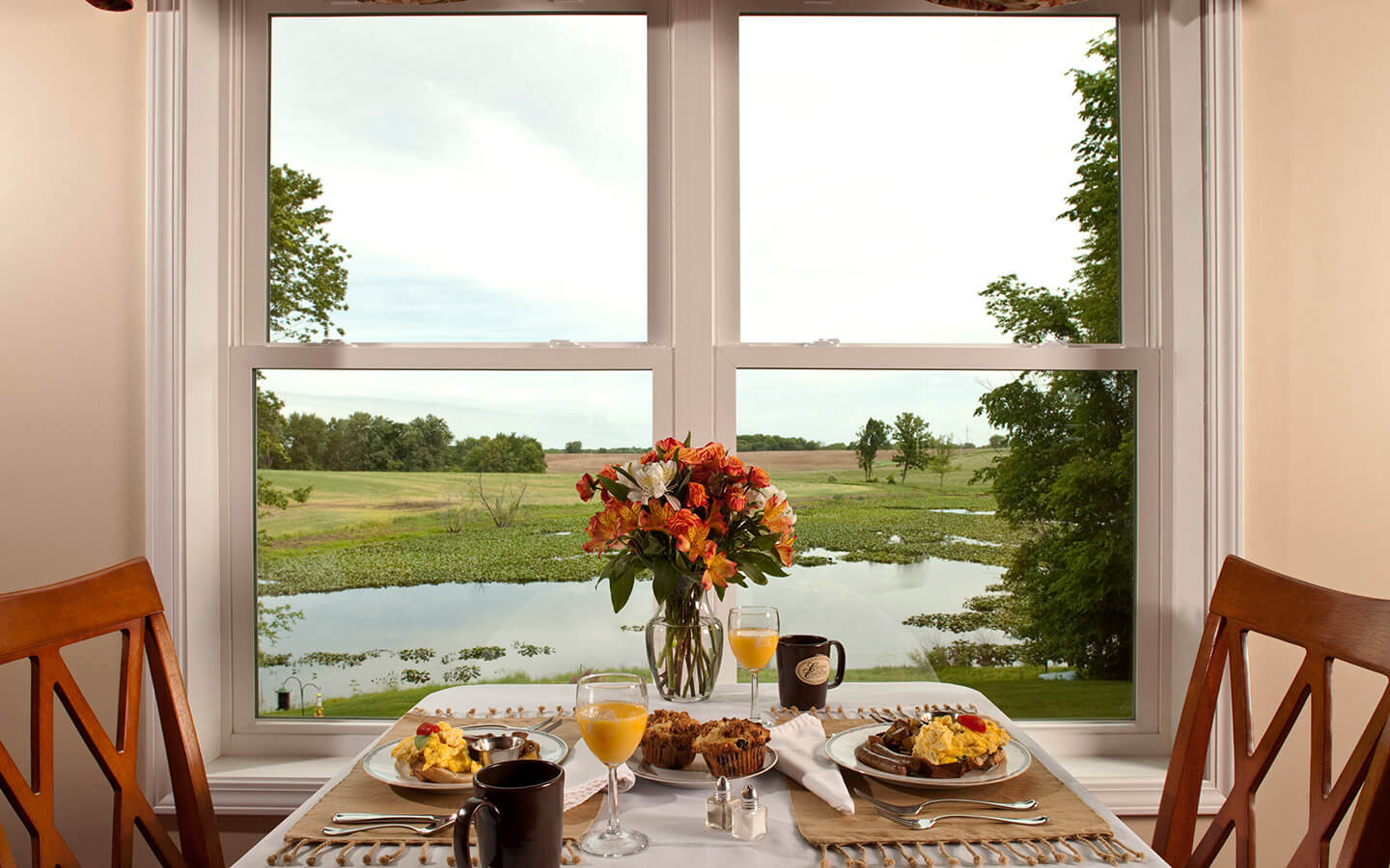 breakfast on a table by a window with a view of the water on a sunny day in Michigan