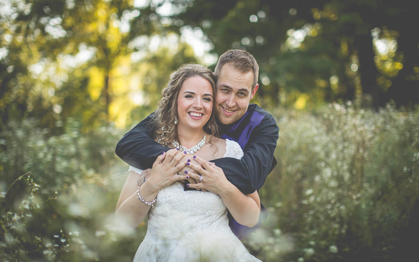 Michigan wedding, bride and groom hugging in a field of flowers