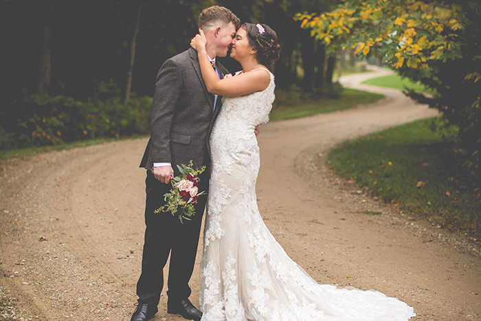 Newlyweds kissing on a country road