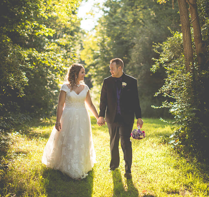 Wedding couple walking on green grass and trees on a sunny day
