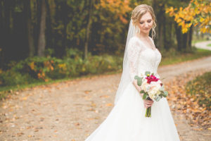 Beautiful bride with bouquet standing on a country dirt road