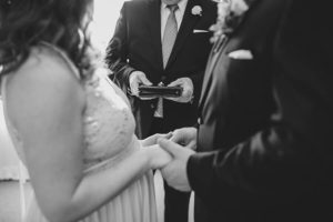 Black and white photo of a bride and groom holding hands during their wedding ceremony