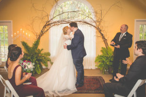 Bride and groom kissing during an indoor wedding ceremony
